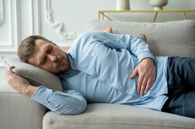 Мужчина страдает от боли в животе, лежа на диване дома, красивый молодой человек, страдающий от боли в животе, лежа на диване дома
