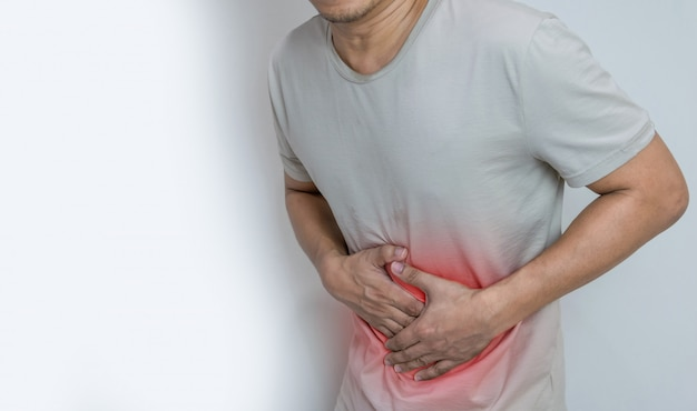 허리 둘레에 손바닥이있는 복통으로 고통받는 사람은 배꼽에 통증과 부상을 보여줍니다.