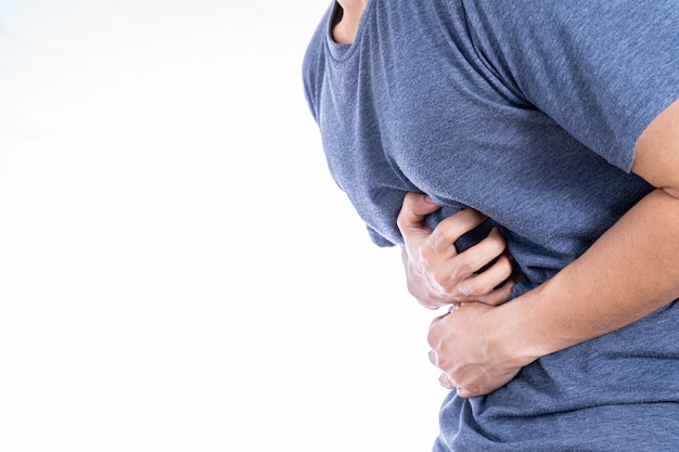 Man suffering from stomach pain and injury isolated white wall.