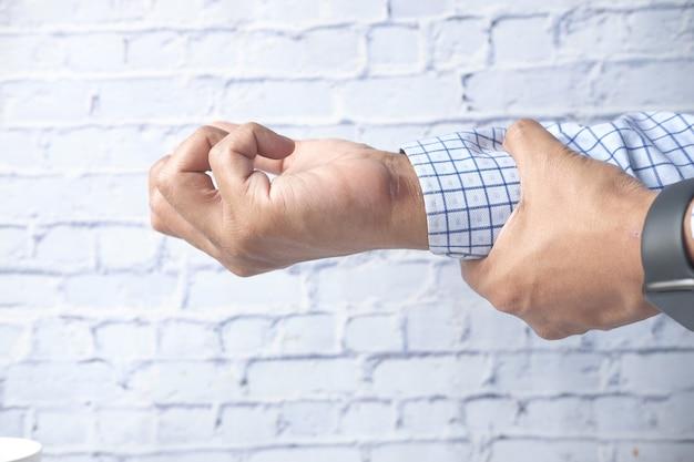 Человек страдает от боли в руке крупным планом