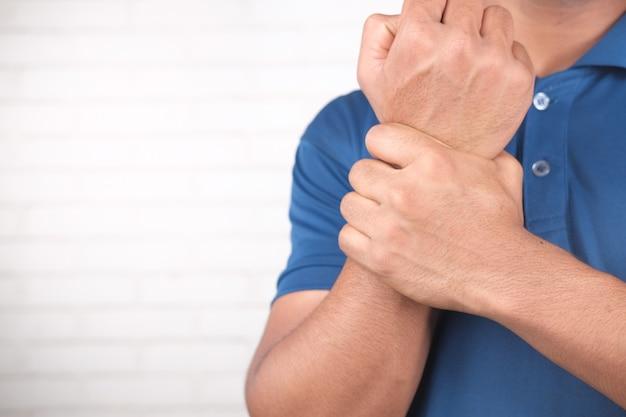 손에 고통을 겪고 남자를 닫습니다.