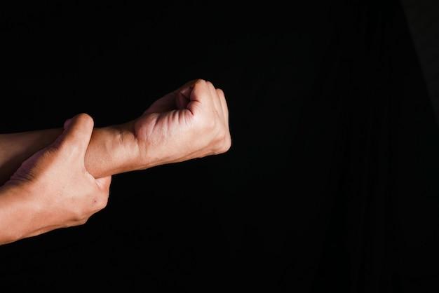 Человек страдает от боли в руке, изолированной на черном