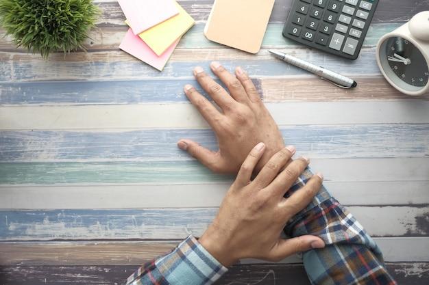 Человек страдает от боли в руке на столе с стационарным