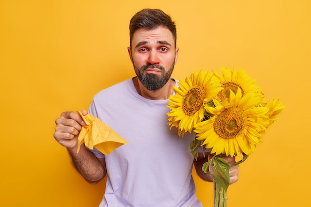 男はアレルギーに苦しんでいます鼻水があります赤い涙目は組織を保持します黄色に分離されたヒマワリの花束を保持します