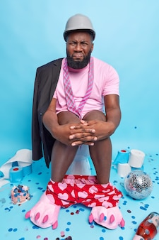 Man suffers from constipation keeps hands on knees frowns face to reveal pain dressed in domestic clothing poses in rest room on toilet bowl reveals himself
