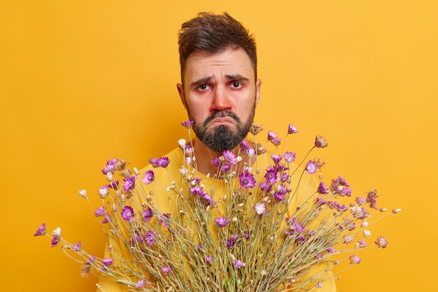 L'uomo soffre di rinite tiene un mazzo di fiori reagisce agli allergeni ha gli occhi rossi e acquosi ha un'espressione infelice posa sul giallo