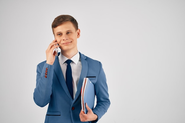 Man in a suit blue folder talking on the phone professional work