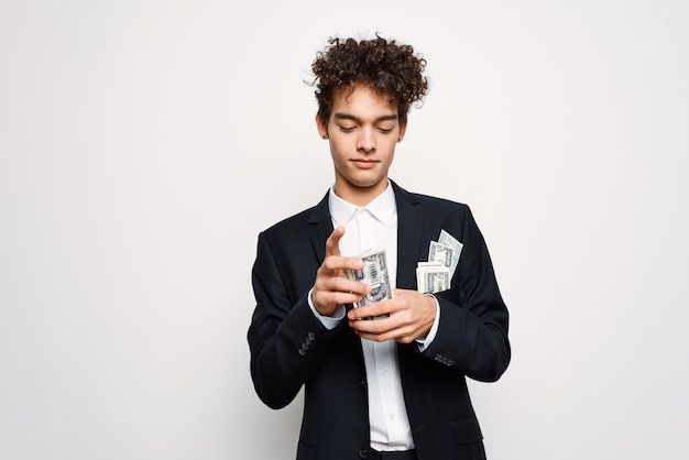 Man in a suit a bundle of money in the hands of a businessman selfconfidence