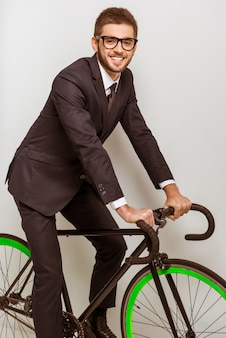 A man in a suit climbed a bicycle and smiles.