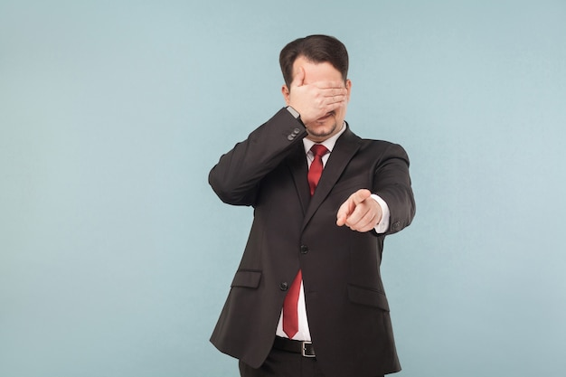 Man in suit closed eyes and pointing finger at camera