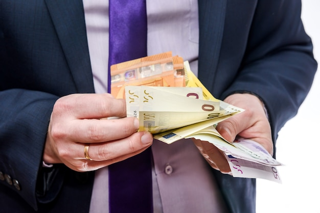 Man in suit counting euro banknotes isolated