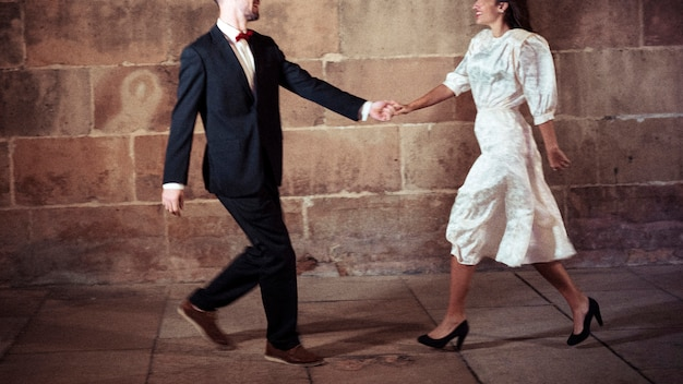 Man in suit dancing with woman in street