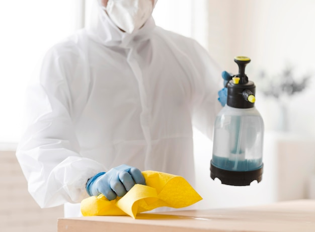 Man in suit disinfecting table close-up