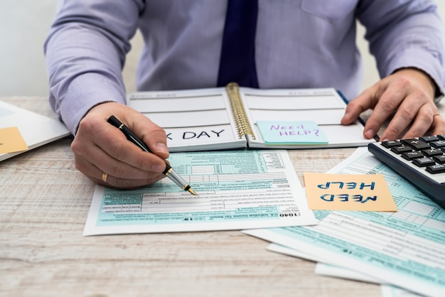 Man in a suit fills out the usa individual 1040 tax form. tax time. accounting concept