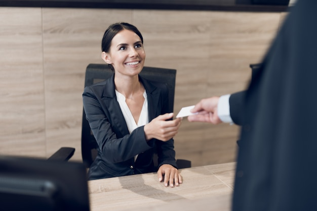 A man in a suit gives his business card to the secretary.
