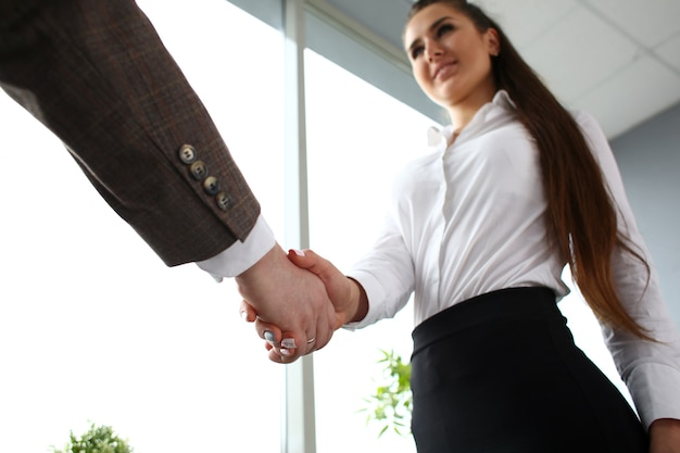 Man in suit gives his hand to businesswoman in office