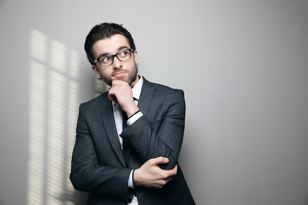 A man in a suit and glasses thinks and touches his chin on a gray wall