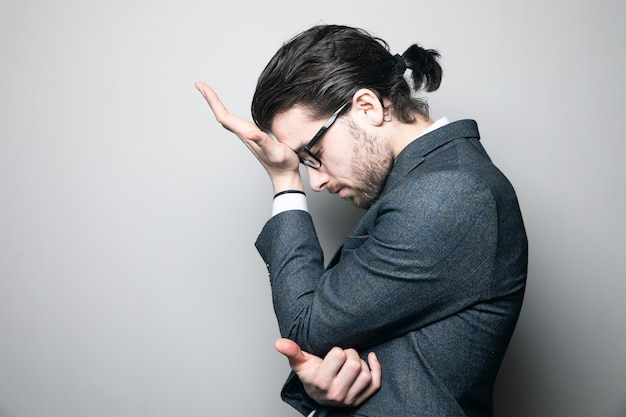 Man in suit and glasses tired on gray wall