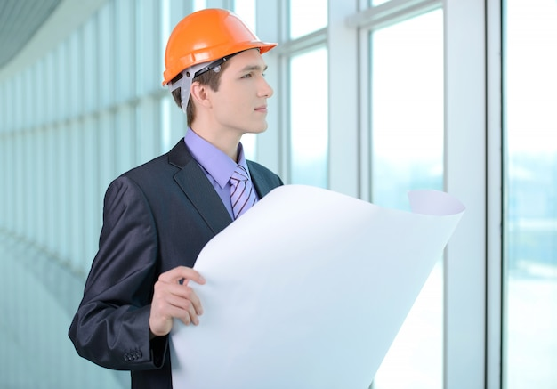 A man in a suit and helmet looks at a construction plan.