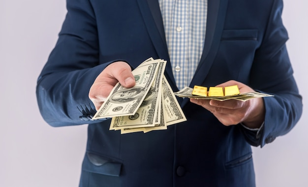 Man in suit hold money dollar bills and gold bar. business success