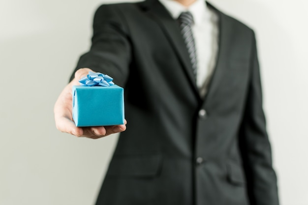 Uomo in un vestito che tiene una piccola scatola regalo blu