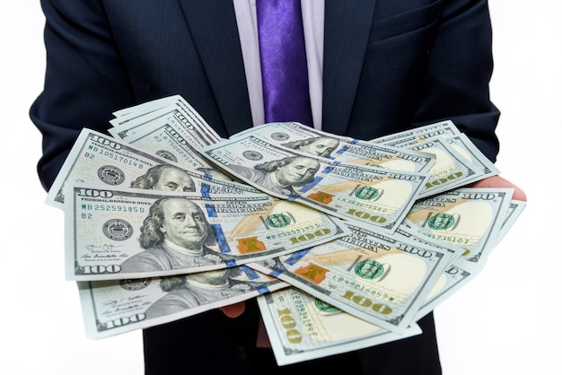 Man in suit holding dollar banknotes close up