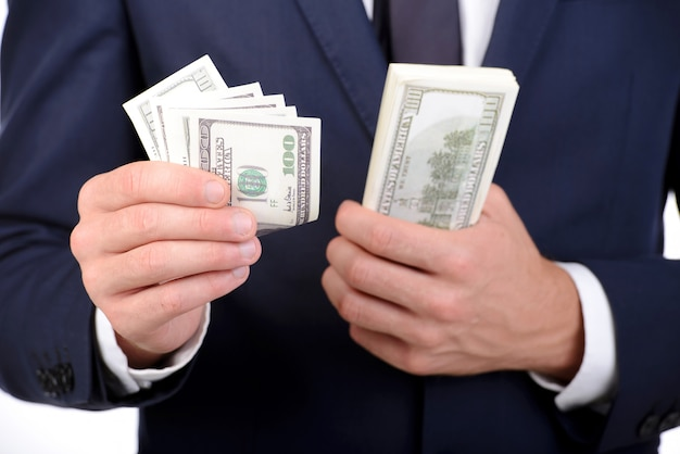 Man in suit holding dollars in his hands.