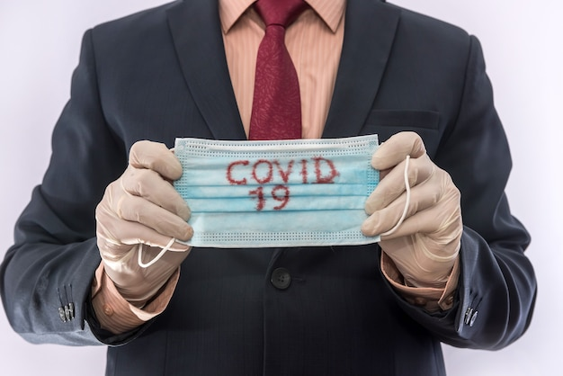 Man in suit holding medical protective mask with text covid19. epidemic