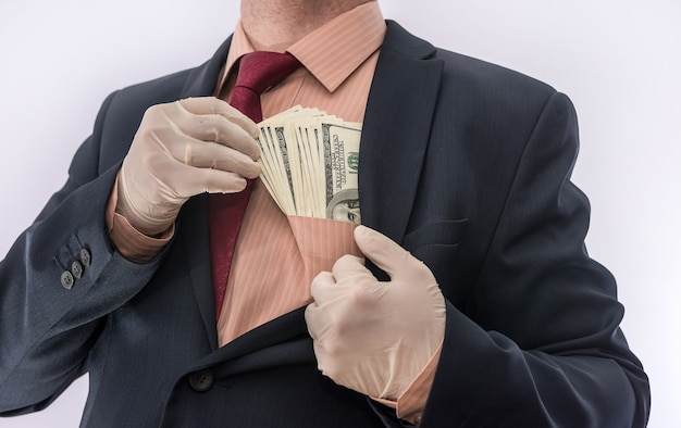 Man in suit holding money dollars 100 bills in medical gloves  for safety.  coronavirus crisis. covid-19
