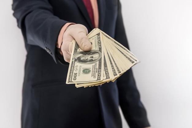 Man in suit holding money dollars 100 bills in medical gloves  for safety.  coronavirus crisis