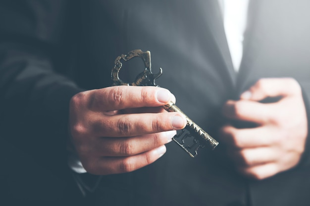 Man in suit holding old key