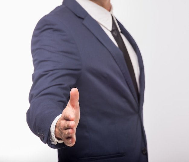 Man in suit holding open palm to greet somebody.