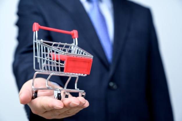 Man in suit holding small shopping trolley in hand