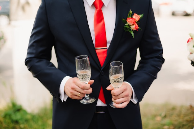 Man in a suit holding two glasses of champagne