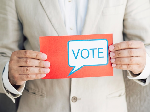 Man in suit holding a voting message