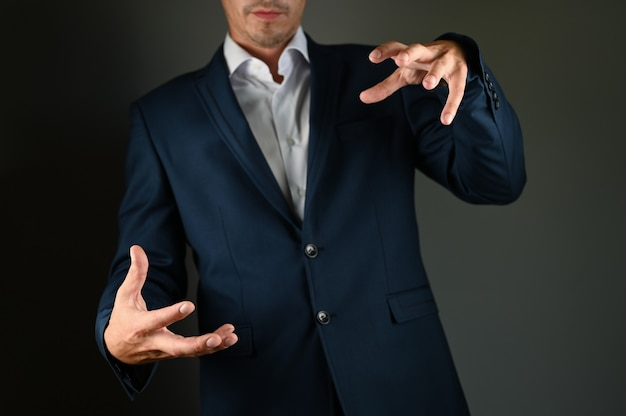 A man in a suit imitates holding an object. a man in a suit spreads his hands on a black space. concept: a positive message in business.