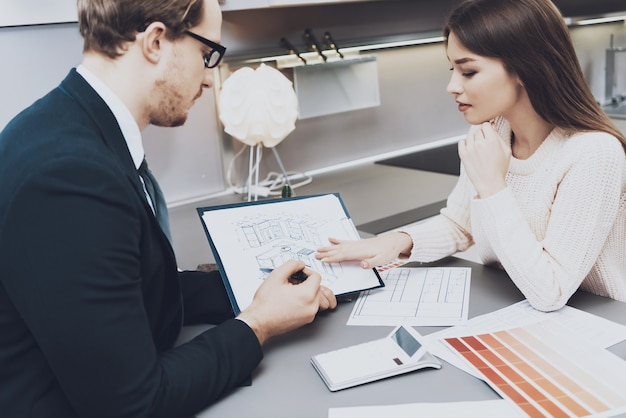 Man in suit is showing blueprints to female in kitchen store