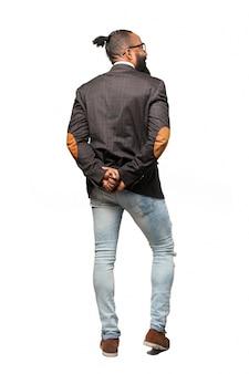 L'uomo in giacca e jeans con le mani per eseguire il