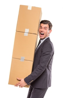 A man in a suit lifted many boxes above himself.