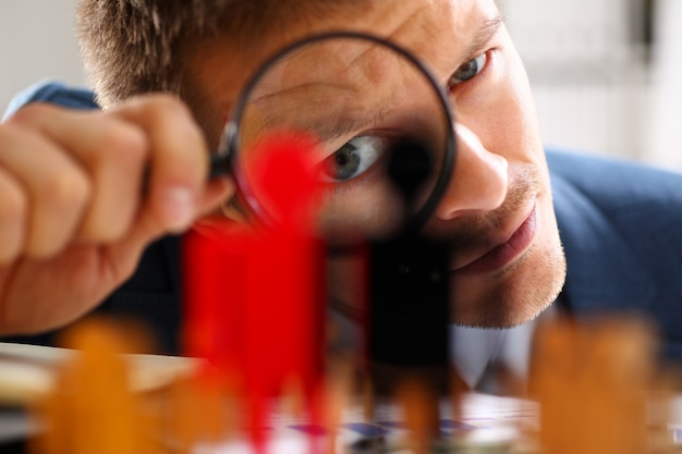 Man in suit look thru loupe on statuettes closeup in office. success hr assessment people headhunt inspector applicant exchange concept