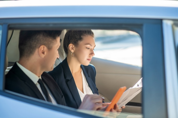 Man in a suit looking at woman with documents in car