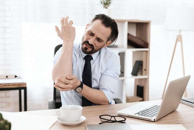 A man in a suit looks at an elbow. it hurts.