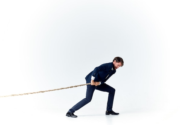 A man in a suit pulls the rope emotion work office