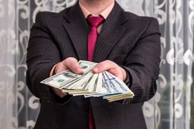 Man in suit showing dollar banknotes, close up