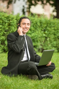 Man in suit sitting at lawn with laptop.