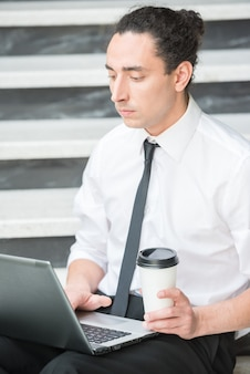Man in suit sitting at stairs in office and using laptop.