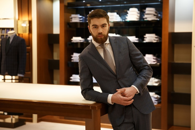 Man in suit standing near the table shop