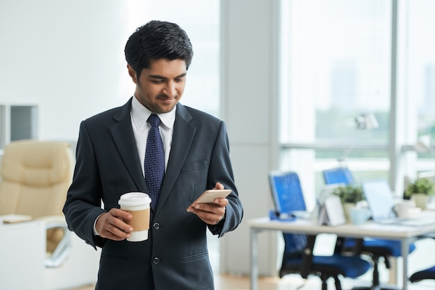 Man in suit standing in office, holding takeaway coffee and using smartphone