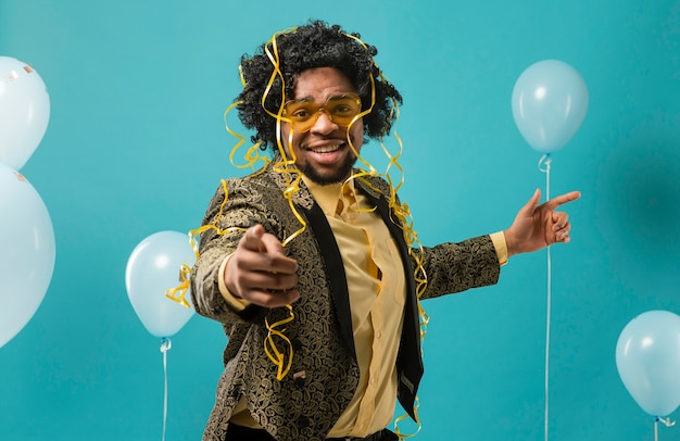 Man in suit and sunglasses at party with balloons pointing