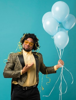 Man in suit and sunglasses at party with balloons portrait